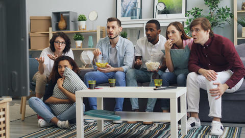 Youth watching tragic news on TV at home expressing negative emotions fear Footage