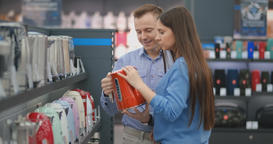 Young couple man and woman in appliances store chooses an electric kettle on the Footage