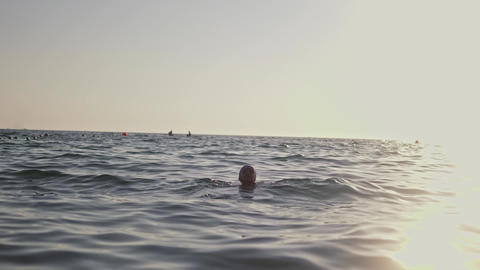 Little young girl learning to swim in the sea GIF