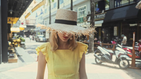 Young Beautiful woman in straw hat walk straight to the camera and smiles Footage