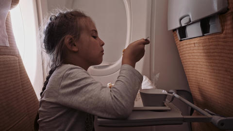 The child is flying on an airplane to rest. A girl sitting near the window and Footage