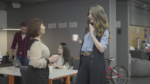 Mature woman talking with her young stylish colleague in modern office. Bearded Live Action