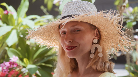 Portrait of beautiful young woman with straw hat on a sunny day looking at Footage