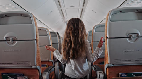 Inside airoplane, child walking in airplane cabin, little cute girl walks aisle Live Action