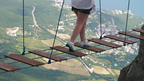 Woman walking by suspension bridge Live Action