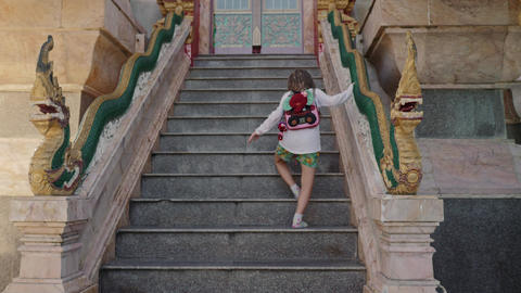 Little tourist girl walk upstairs to buddha temple Footage