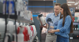 The couple in casual clothes in the electronics store chooses an electric kettle Footage