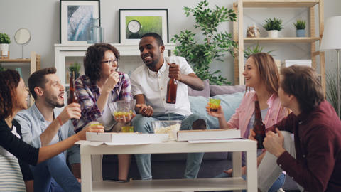 Multiracial group of young people celebrating at home with pizza and alcohol Footage