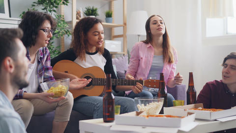 Multiethnic group of friends singing and playing the guitar at home during party Footage