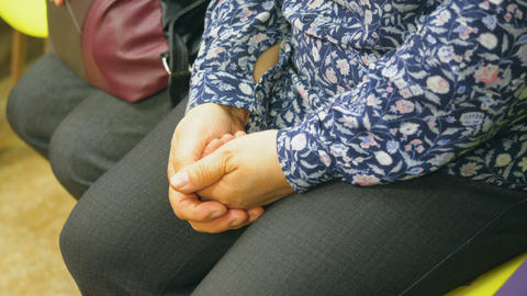 Woman is sitting and keeping her hands joint on her legs. Hands close-up Footage