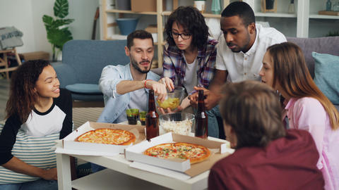 Young people men and women eating and chatting during indoor party in apartment Footage