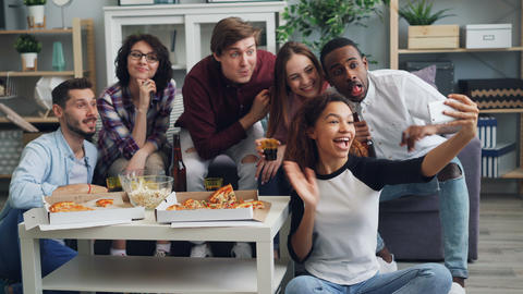 Cheerful youth taking selfie with pizza and drinks at party using smartphone Live Action
