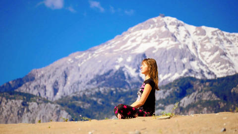 Young woman sitting calm cross-leged on the sand Footage