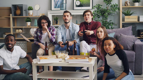 Young happy friends playing video games talking eating having fun at home party Footage
