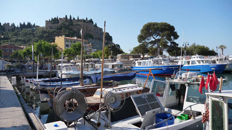 Panning harbour Cassis showing boats town people provence france GIF