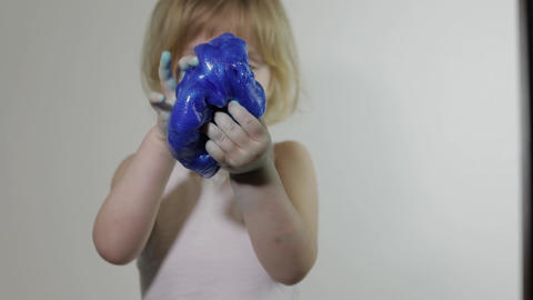 Child having fun making slime. Kid playing with hand made toy slime ビデオ
