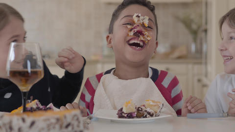 Happy kids fooling around while eating the cake. The kids are laughing. African Footage