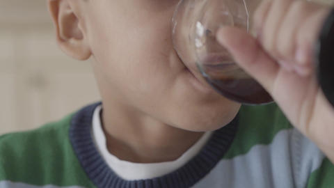 Close-up of a half face of an African American boy drinking a juice from a wine Live Action
