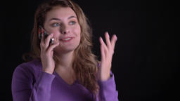 Portrait of glad blonde woman having a voice call on smartphone on black Footage
