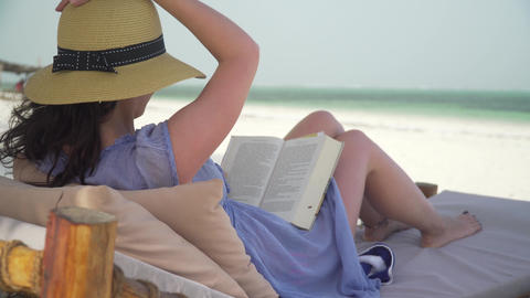Young woman reading book on white beach by ocean Footage