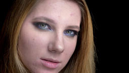 Closeup shoot of young beautiful female face with stunning makeup looking at Footage