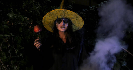 Wicked Witch with enchanted apple in Halloween Horror Scene Footage