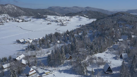 Aerial, Tilt Up - Winter Landscape Populated With Cottages And Log Cabins stock footage
