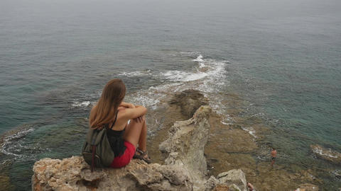 Female tourist with backpack sitting on a rock on clear sky and calm sea Live Action