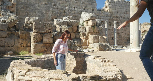 Young female tourists walking in Ancient city Perge, open air antique historical Live Action