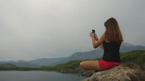 Female tourist sitting on a rock on clear sky and calm sea background Footage
