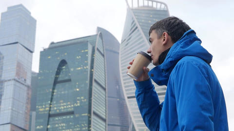 Young man with coffee on Moscow new city background Footage