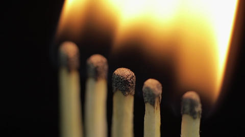 Matches light up one by another in series on black background Live Action