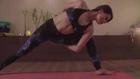 Young flexible woman practicing yoga indoors Live Action