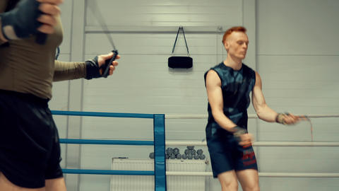 Two boxer training on skipping rope in fight club. Cardio training concept Live Action