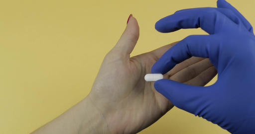 Doctor hand dressed in blue medical glove puts one white pill into woman hand Footage