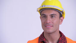 Face of young happy Hispanic man construction worker thinking Archivo