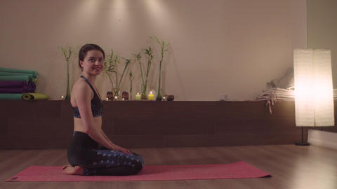 Smiling woman sitting in yoga studio Live Action