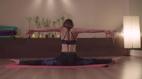 Flexible woman practicing yoga in nice studio Live Action