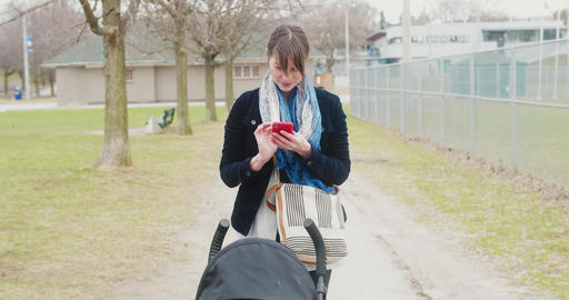 Young woman sends a text message while pushing a stroller ビデオ