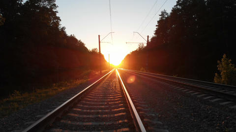 Sparkling railroad going thru dense wood at sunset in Ukraine Footage