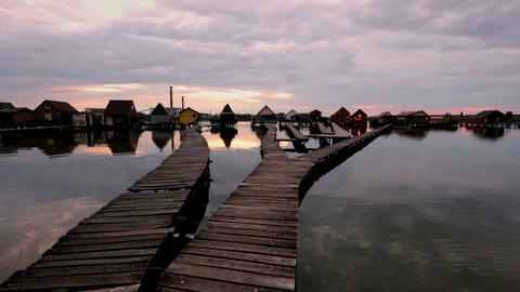 Sunset over lake Bokod with wooden pier and floating houses, Hungary Footage