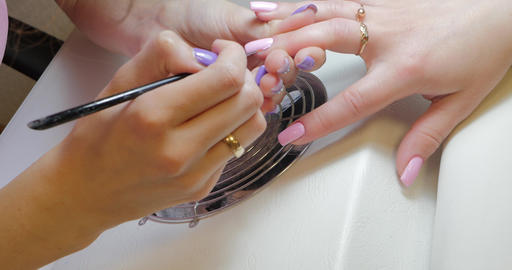Manicure master makes corrections to pink color gel polish ビデオ