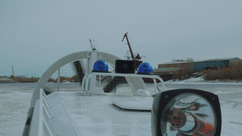 Small hovercraft on frozen river with working propeller Archivo