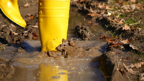 Dirty rubber boot steps into dirty water in slow motion Live Action