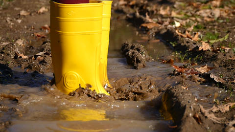 Dirty rubber boot steps into dirty water in slow motion Stock Video Footage