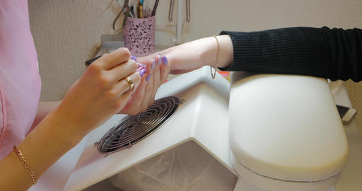 Manicure master applies pink color gel polish ビデオ