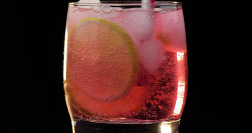 Making a refreshing red drink cocktail in a glass with ice, and lime Footage