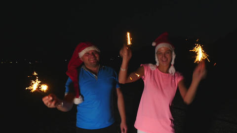 Young man and woman in Christmas hats dancing with Bengal lights Footage