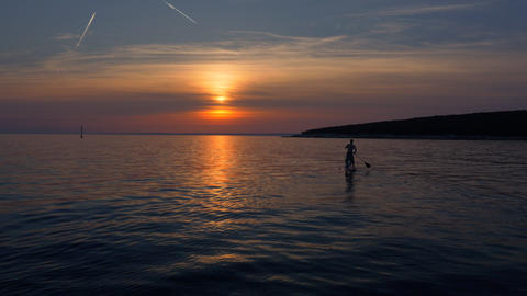 Aerial - Young man stand up paddling towards the sunset Footage