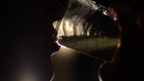 Silhouette of a woman drinking a glass of juice with small sips 01 Footage